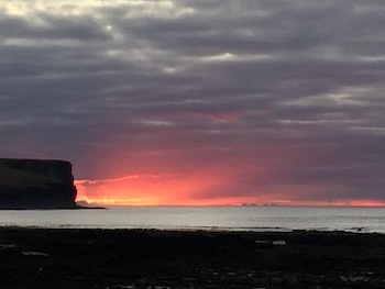 mainland Scotland is ablaze behind Marwick Head, Orkney